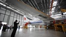 A journalist takes a picture of an Airbus A320 plane under construction for Air China Airlines at the Airbus factory in Tianjin, June 13, 2012. (JASON LEE/REUTERS)