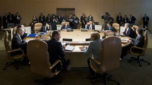 British Prime Minister David Cameron and German Chancellor Angela Merkel, front from left, share a word during a G8 working session with other world leaders during the G8 Summit at the Deerhurst Resort in Hunstville, Ont., Saturday.