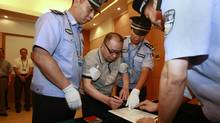 Alleged smuggling kingpin Lai Changxing (C) is escorted by policemen as he signs a warrant issued for his arrest at the Beijing Capital International Airport in Beijing, July 23, 2011 in this photo distributed by China's official Xinhua News Agency. (XINHUA/REUTERS)
