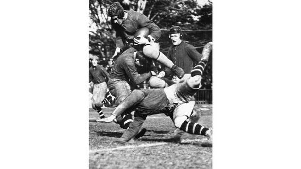 Victorious University of Toronto Varsity Blues' Smirle Lawson carries the ball in the first Grey Cup game on Dec. 4, 1909. The Blues defeated the Toronto Parkdale Canoe Club at Rosedale Field by a score of 26-6.
