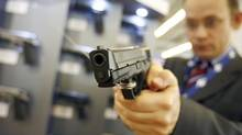 A visitor tests a Smith & Wesson gun model M&P9, 9 millimetre, at the MILIPOL International State Security Exhibition in Paris October 9, 2007. (© Regis Duvignau/Reuters)