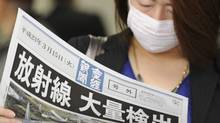 "A masked woman reads an extra newspaper with the banner reading, ""Radiation Detected in Large Amount,"" at Osaka, western Japan, on Tuesday March 15, 2011. (Kyodo News/AP/Kyodo News/AP)"