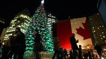 People gather around and pass by a Christmas tree after it was lit by singers Diana Krall and husband Elvis Costello during a lighting celebration in Vancouver on December 8, 2009. (DARRYL DYCK)