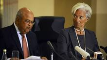 International Monetary Fund Managing Director Christine Lagarde (R) reacts next to South African Finance Minister Pravin Gordhan during a media briefing in Pretoria January 6, 2012. (STRINGER/REUTERS)