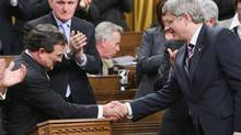 Finance Minister Jim Flaherty, left, is congratulated by Prime Minister Stephen Harper on Tuesday after delivering the government's budget speech. (Sean Kilpatrick/Sean Kilpatrick/The Canadian Press)