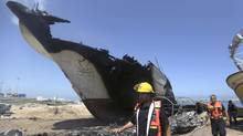 Palestinian firefighters walk around a boat hit in an missile strike at the port in Gaza City, Friday, July 11, 2014. (Hatem Moussa/AP)