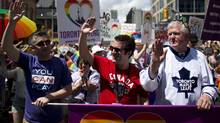 General Manager of NHL team, the Toronto Maple Leafs, Brian Burke, far right,  his son Patrick Burke, far left, and comedian Rick Mercer march during the Gay Pride parade in Toronto July 1, 2012. (Reuters)