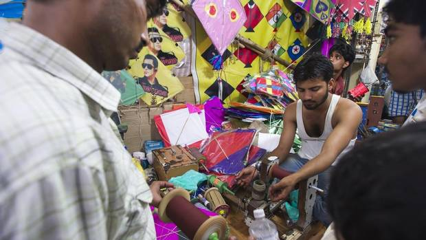 Men prepare reels of line in a kite flying shop in Old Delhi. (Simon de Trey-White for The Globe and Mail)