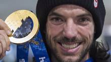 Canadian short track speedskater Charles Hamelin holds up his Sochi 2014 Winter Olympic gold medal on his arrival back from the games at Trudeau Airport in Montreal, Tuesday, February 25, 2014. (Graham Hughes/THE CANADIAN PRESS)