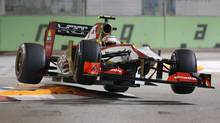 Hispania Racing Team Formula One driver Narain Karthikeyan of India is airborne as he goes over the chicane during qualifying for the Singapore Formula One Grand Prix on the Marina Bay City Circuit in Singapore, Saturday, Sept. 22, 2012. (Wong Maye-E/AP)