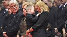 Christine Russell, wife of Sgt. Ryan Russell, has an intimate moment with her son, Nolan, during her husband's funeral. His parents are at left. (Pool/Nathan Denette/The Canadian Press)