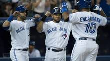 Toronto Blue Jays first baseman Edwin Encarnacion, right, celebrates with Blue Jays teammates Jose Bautista, left, and Melky Cabrera, centre, after hitting a grand slam against the Baltimore Orioles during sixth inning AL baseball action in Toronto on Thursday, May 23, 2013. (Nathan Denette/THE CANADIAN PRESS)