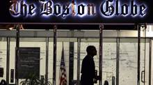 A security guard walks past the entrance of The Boston Globe. Its owner, New York Times Co., has put The Boston Globe up for sale even though it's likely to get only one-tenth of the $1.1-billion it paid. (Charles Krupa/AP)