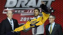 Seth Jones, a defenceman, pulls on a Nashville Predators sweater after being chosen 4th overall in the first round of the NHL hockey draft, Sunday, June 30, 2013, in Newark, N.J. (Associated Press)