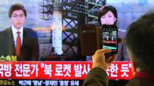 South Korean man uses his smartphone to take a television screen reporting a news about North Korea's rocket launch at Seoul Railway Station in Seoul, South Korea, Wednesday, Dec. 12, 2012. (Ahn Young-joon/The Associated Press)