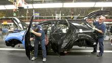 Workers install parts onto a GMC Terrain vehicle at the CAMI Automotive Inc. plant assembly line in Ingersoll, Ont. (Norm Betts/Bloomberg/Norm Betts/Bloomberg)