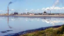 A tailings pond reflects the Syncrude oilsands mine facility near Fort McMurray, Alta. (Jeff McIntosh/The Canadian Press)