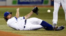 Toronto Blue Jays pitcher R.A. Dickey makes a play from the ground against the Tampa Bay Rays during the third inning of their MLB American League baseball game in Toronto, September 27, 2013. Toronto won 6-3. (MARK BLINCH/REUTERS)