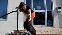 Erika Podlovics of the Wterloo, Ont., tech company Kik pets her dog Wellington outside her work. The fast-growing 25-person startup firm encourages staff to bring their dogs to work, play ping-pong in the games room and has catered meals daily for programmers. (Michelle Siu for The Globa and Mail/Michelle Siu for The Globe and Mail)