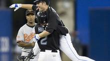 Toronto Blue Jays batter Adam Lind leaps into the arms of Aaron Hil after hitting a game-winning double off Baltimore Orioles pitcher Danys Baez during the 10th inning in Toronto on Saturday. (FRANK GUNN)
