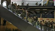 Soldiers ride an escalator as they arrive for duty at the Excel center at the London Olympic Games, 29 July, 2012. (KAI PFAFFENBACH/REUTERS)