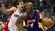 Toronto Raptors guard Jose Calderon, left, battles for the ball with Los Angeles Lakers guard Kobe Bryant, right, during first half NBA basketball action in Toronto on Sunday. (Nathan Denette)