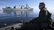 A crewman from the frigate HMCS Toronto looks back at his ship from a zodiac while on manoeuvres on Frobisher Bay in the Canadian Arctic in this August 19, 2009 file photo. (ANDY CLARK/REUTERS)