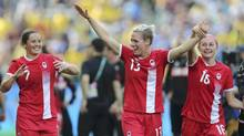 Canada's Rhian Wilkinson, Sophie Schmidt and Janine Beckie celebrate after a match in Rio. The Canadian women's soccer team won bronze. (Fernando Donasci/Reuters)