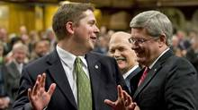 Tory MP Andrew Scheer jokingly tries resist Prime Minister Stephen Harper and NDP Leader Jack Layton as they escort him to the Speaker's chair in the House of Commons on June 2, 2011. (Adrian Wyld/THE CANADIAN PRESS)