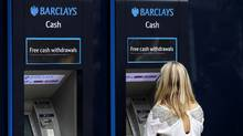 A customer uses a Barclays ATM in central London, July 23, 2010. (ANDREW WINNING/REUTERS)