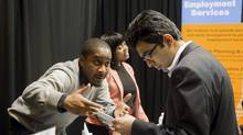An exhibitor talks to a job seeker at the Bi-lingual Job Fair and Training Expo in Toronto on Thursday March 8, 2012 . (Chris Young/Chris Young for The Globe and Mail)