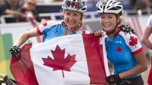 Canada's Catharine Pendrel, left, won gold and teammate Emily Batty womn silver in the women's cross-country event at Cathkin Braes mountain bike trails at the Commonwealth Games in Glasgow, Scotland on Tuesday, July 29, 2014. (The Canadian Press)