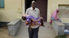 Musa carries the body of his son Ahmen, 8, from Banadir Hospital after he died. (Peter Power/The Globe and Mail/Peter Power/The Globe and Mail)