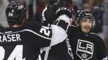 Los Angeles Kings defenceman Slava Voynov (R) celebrates his first period goal against the Chicago Blackhawks with teammates Kyle Clifford (obscured) and Colin Fraser (24) during Game 4 of the NHL Western Conference final playoff in Los Angeles, California, June 6, 2013. (DANNY MOLOSHOK/REUTERS)