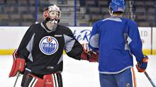 Canadian Olympic women's team goalie Shannon Szabados gives a low-five to Nail Yakupov as she takes part in the Oilers practice in Edmonton, Alta., on Wednesday March 5, 2014. (JASON FRANSON/THE CANADIAN PRESS)