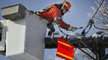 Enwin Utilities employee Mitch Prier helps repair damaged power lines in the Toronto suburb of Scarborough on Dec. 26, 2013. (KEVIN VAN PAASSEN/THE GLOBE AND MAIL)