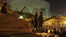 Members of Egypt's Republican Guard Force stand atop a tank as protesters opposing President Mohammed Morsi demonstrate in front of the presidential palace in Cairo, Dec. 18, 2012. (Khaled Abdullah/REUTERS)