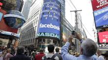 A man stops to photograph Nasdaq in Times Square as Facebook has its IPO, Friday, May 18, 2012, in New York. (Richard Drew/AP)