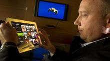 Telus chief marketing officer shows the Optik TV Smart Remote App on an iPad. 'We're trying to do simple things well.' (Peter Power/The Globe and Mail)