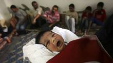 Palestinian newborn Rajab Erdogan is held by his father wrapped in a Turkish flag for members of the media, at their home in the southern Gaza Strip refugee camp of Khan Younis , Sunday, June 6, 2010. (Eyad Baba/Eyad Baba/Associated Press)