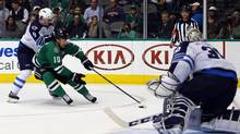 Dallas Stars' Patrick Sharp (10) advances the puck as Winnipeg Jets' Jacob Trouba (8) defends and goalie Connor Hellebuyck (30) blocks the goal during the third period of an NHL hockey game, Thursday, Jan. 7, 2016, in Dallas. (Mike Stone/AP)