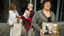 Lorraine Johnson, foreground, holds a photo of her son, Brian David Geisheimer, 30, as Deb Nolet, with a photo of her daughter, Sarah Louise Charles, talks to Kim Young outside the B.C. Coroner's Service in Burnaby on Sept. 7, 2016. (John Lehmann/The Globe and Mail)