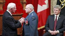With Prime Minister Stephen Harper looking on in the Senate chamber, Governor-General David Johnston bestows the Meritorious Service Cross on Lieutenant-General Charles Bouchardlooks on during a ceremony honouring troops who served in the NATO-led mission in Libya on Nov. 24, 2011. (DAVE CHAN/Dave Chan/Reuters)