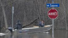 A woman rests her head on her hand as she travels through a flooded residential area of Gatineau, Que., on Monday. (Adrian Wyld/The Canadian Press)
