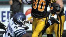 Hamilton Tiger-Cats wide receiver Chris Williams runs the ball past Toronto Argonauts defender Jeff Johnson (L) during the second half of their CFL football game in Hamilton September 3, 2012. (MIKE CASSESE/REUTERS)