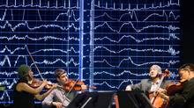 Members of the Afiara String Quartet perform while a computer display shows the musicians' brain activity as they play together. The fundraising concert held on Sept. 5, 2014, showed off the unique capabilities of the newly completed LIVELab (Large Interactive Virtual Environment) at McMaster University in Hamilton. The 100-seat performance hall is designed to enable neuroscientists and other researchers to monitor both performers and audience members in an effort to better understanding the social underpinnings of music. The space will be used for a host of other commercial and research projects, from engineering better hearing aids to studying the effectiveness of dance as a therapy for Parkinson's disease. (Glenn Lowson For The Globe and Mail)