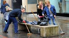 Members of the public help clean up Manchester, England, on Aug. 10, 2011, following a night of violence that occurred during Britain's worst riots in decades. (ANDREW YATES/AFP/Getty Images)