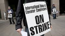 Striking International Union of Elevator Constructor elevator mechanics Shaun Bryrne and Andrew McKinnon are among many elevator workers picketing outside the Toronto Eaton Centre shipping and receiving garage entrance in Toronto on Friday, June 7, 2013. (Deborah Baic/The Globe and Mail)