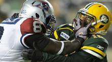 Montreal Alouettes' Kerry Carter (L) straight arms Edmonton Eskimos' Donovan Alexander during their CFL football game in Edmonton September 23, 2011. REUTERS/Dan Riedlhuber (DAN RIEDLHUBER)