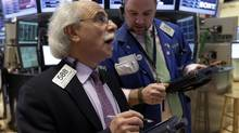 Traders Peter Tuchman, left, and Kevin Lodewick work on the floor of the New York Stock Exchange. (Richard Drew/AP)